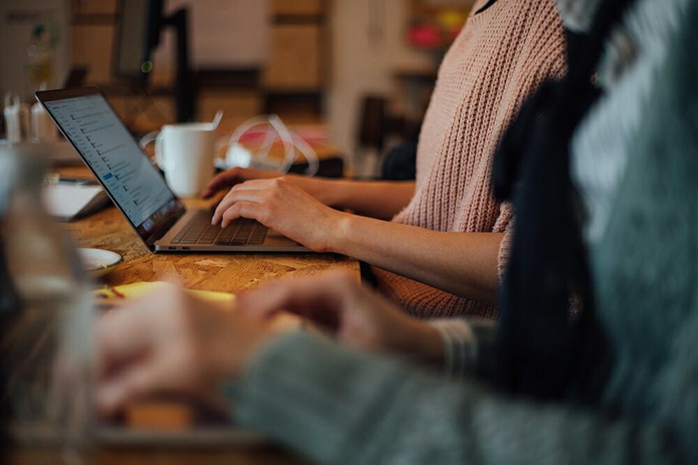 Nahaufnahme Hände auf einer Laptoptastatur